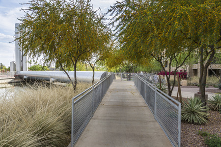 Pedestrian ramp and blooming mesquite trees at the Soleri Bridge in Scottsdale Arizona. Stock Photo