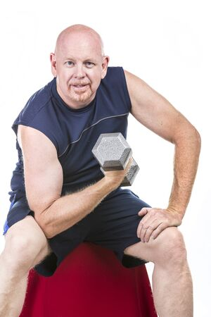 Fit senior male doing weight training with dumbbells isolated on white. Stock Photo