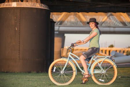 Cute and trendy young lady riding a bicycle at sunset in an urban setting for a modern youth lifestyle concept.