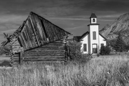 emery: An old abandoned Mormon Church and a cabin built by Mormon settlers in Emery Utah photographed in black and white.