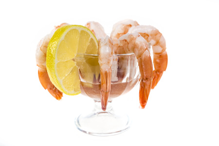Popular appetizer shrimp cocktail in a glass serving bowl isolated on white.