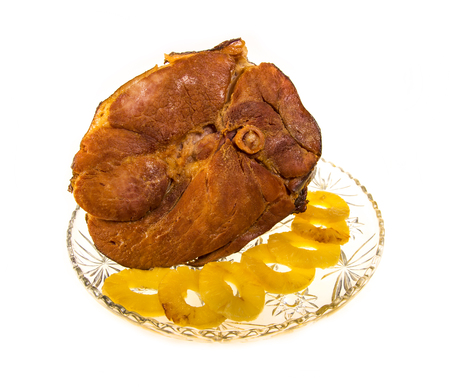 Large shank ham roasted and glazed with pineapple isolated on white.