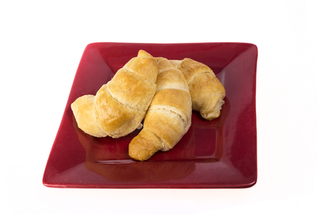 buttery: Three fresh flakey buttery croissants on a red plate and isolated on  white. Stock Photo