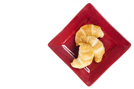 buttery: Three fresh flakey buttery croissants on a red plate and isolated on white with copyspace. Stock Photo
