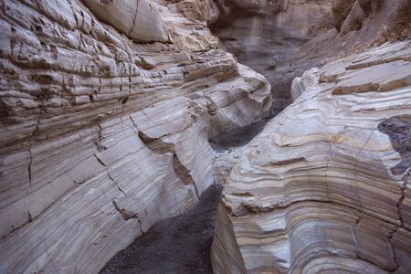 Canyon wall in Mosiac Canyon at Death Valley California showing a smooth eroded mosaic surface with many mineral layers folded and deformed by pressure.