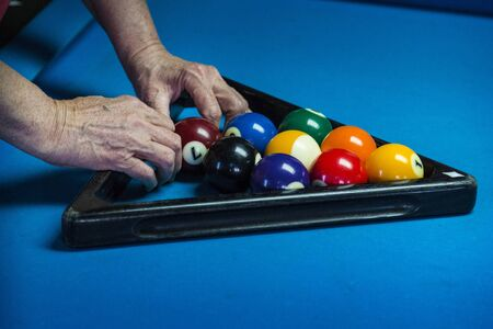 Closeup of female hands racking up billiard balls. Stock Photo