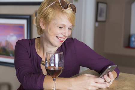 Woman using social media on a smart phone at a casual bar while drinking wine.