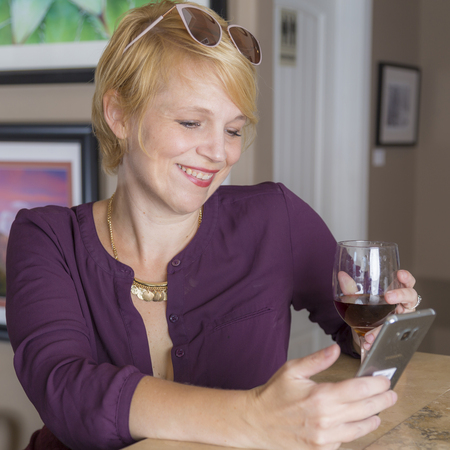 Woman using social media at a casual bar while drinking wine.