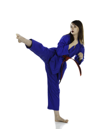 Female red belt student practicing Tae Kwon Do martial arts moves.