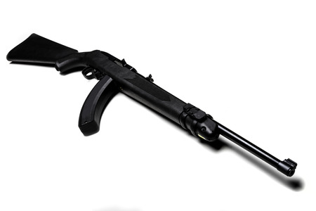 Black Ruger 22 caliber rifle with a high-capacity clip and laser sight isolated in white. Imagens