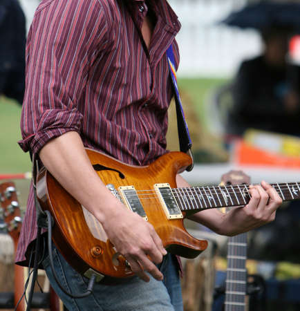 Musician playing electric guitar during an outdoor festival