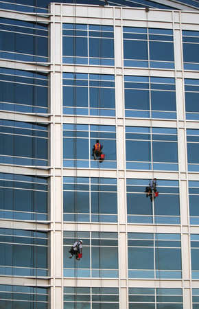 Three window washers descend on ropes high above the city. The building is a very modern glass structure. Stock Photo