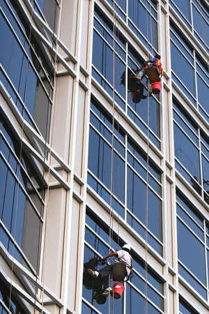 Two window washers descend on ropes high above the city. The building is a very modern glass structure.