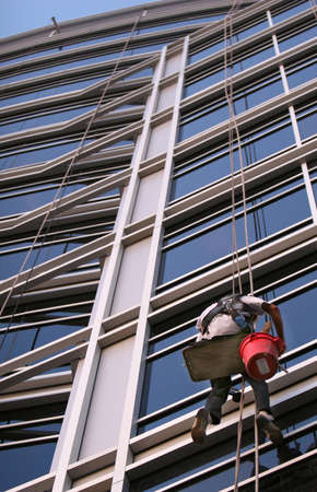 A window washer descend on ropes high above the city. The building is a very modern glass structure. Stock Photo