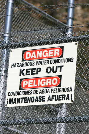warns: A sign warns of hazardous water conditions on a barbed wire fence