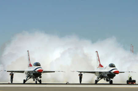 concluded: Flight crews tests the performance of a jet fighters engines on the tarmac. Smoke billows out the back as the tests are concluded.