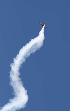 A stunt plane clims straight up as it leaves a smoke trail spiraling below Foto de archivo