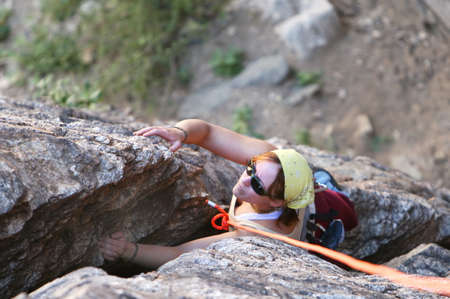 belay: A young woman climbs a crack in the rock. She is secured by top rope belay.
