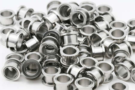 lobes: A big pile of screw on flesh tunnels. These are used in stretched ear lobes. Stock Photo
