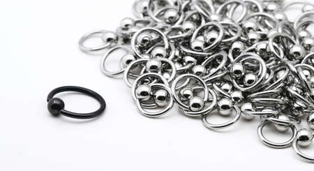 Stand out from the crowd. A lone black captive ring is separated from the rest of the silver rings. photo