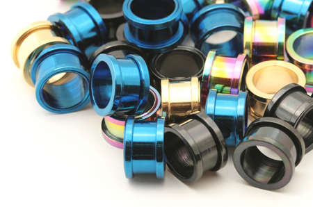 A big pile of colorful titanium screw on flesh tunnels. These are used in stretched ear lobes.