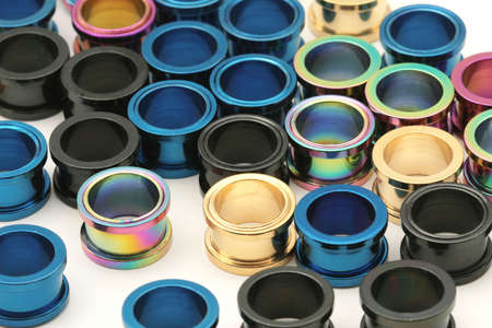 titanium: A big pile of colorful titanium screw on flesh tunnels. These are used in stretched ear lobes.