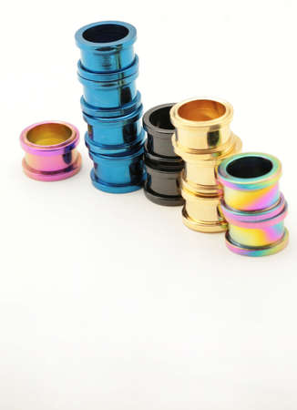 titanium: Five stacks of colorful titanium screw on flesh tunnels. These are used in stretched ear lobes. Stock Photo