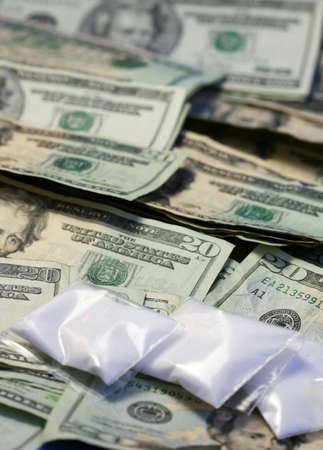 Baggies of cocaine sit onto a pile of american money. (Photographed with sugar - please dont send the police for me!) photo