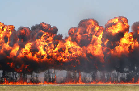 Giant Explosion! A wall of fire explodes on an open field.  photo