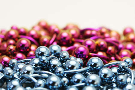 titanium: A bulk pile of titanium anodized navel belly rings sitting on a white background