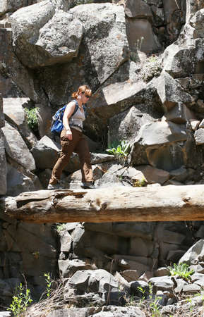 A young hiker walks across a log in a canyon Imagens - 1438478