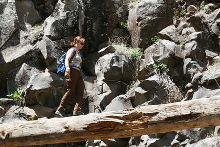 A young girl attempts to cross a log while hiking through a rocky canyon Stock Photo - 1438480