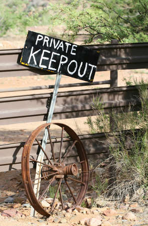 A sign stating 'PRIVATE KEEP OUT' stands in front of a fence alongside an old wheel