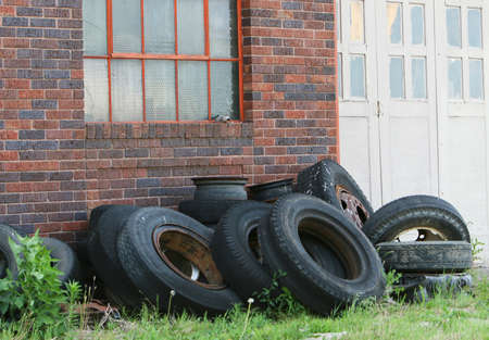 A pile of old tires and rims are resting in front of a red brick building