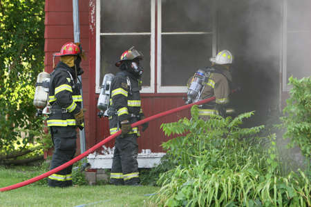 house on fire: Three firemen work to out out a house fire in the midwest.
