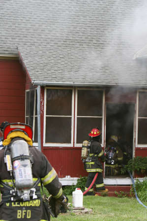 Firemen work to put out a small housefire