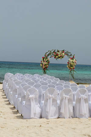 White chairs await guests at a beautiful beachside wedding in Mexico Stockfoto