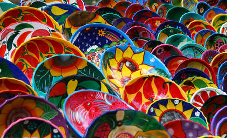Hundred of handmade bowls are arranged neatly on tables in Chichen Itza Mexico. They are beautifully painted with vibrant colors and unique designs.