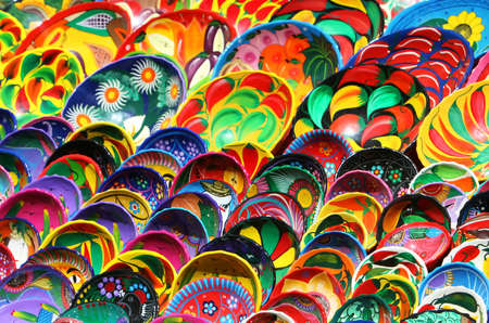Hundred of handmade bowls are arranged neatly on tables in Chichen Itza Mexico. They are beautifully painted with vibrant colors and unique designs. photo