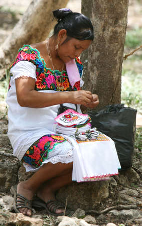 mayan culture: A Mayan woman making decorative pot holders at Chichen Itza in Mexico. The Mayans are very poor and increasingly depend upon selling souvenirs to tourist to make money Stock Photo