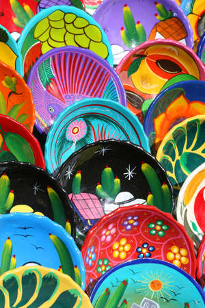 dozens: Dozens of handmade bowls are arranged neatly on tables in Chichen Itza Mexico. They are beautifully painted with vibrant colors and unique designs.