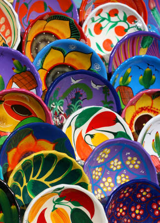 neatly: Hundred of handmade bowls are arranged neatly on tables in Chichen Itza Mexico. They are beautifully painted with vibrant colors and unique designs.