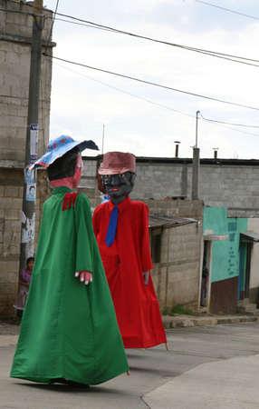 Mensen gekleed in kostuums steltenlopers entertainen locals tijdens deze traditionele Maya-viering