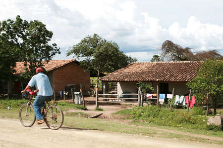 A cycling passes a house on a rural road in Honduras