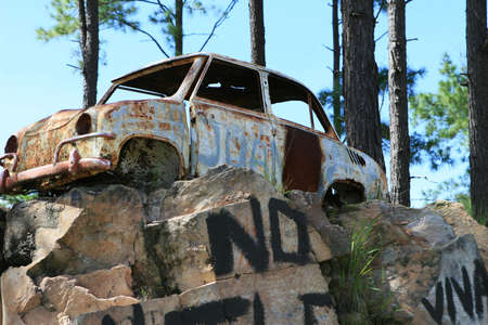 eyesore: A rusty old car resting atop a pile of rocks Stock Photo