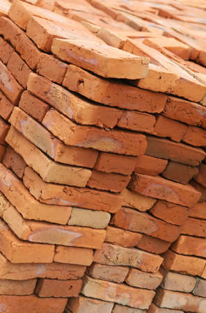 Hand made bricks are stacked and ready to build a house Imagens