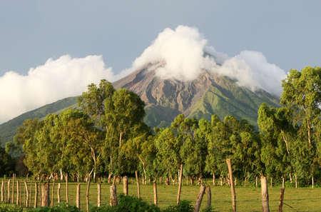 An active volcano looms  over rich, fertile fields below