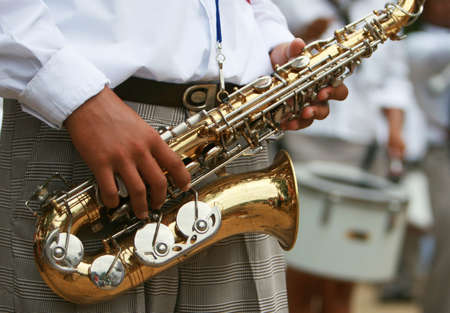 fingering: A saxaphone player marching in a parade