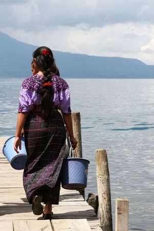 crater lake: Mayan woman gather water at Lago Atitlan, Guatamala Stock Photo