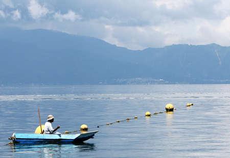 Een zwevende in een kleine boot visser